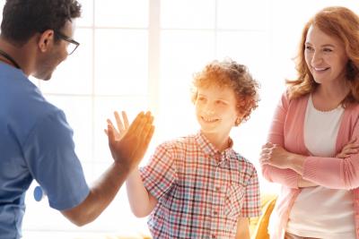 little boy getting a high five from a male nurse